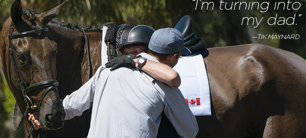 father and son equestrian hugging with horse